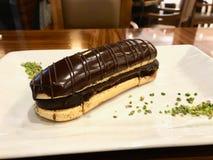 Schokolade Eclairs mit dem Pistazien-Pulver gedient am Restaurant stockbilder