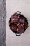 Schokolade in einem Metallvase auf einem Hintergrund des grauen Segeltuches Stockfotografie