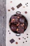 Schokolade in einem Metallvase auf einem Hintergrund des grauen Segeltuches und flehen an Lizenzfreies Stockbild