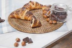 Schokolade, Hörnchen und Haselnüsse auf Holztisch Lizenzfreie Stockfotos