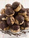 Schokolade Profiteroles auf einem Kuchen-Standplatz Stockbilder