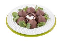 Schokolade profiteroles mit süßer Klumpencreme auf einem weißen backgrou Stockfoto