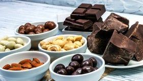 Schokolade, Süßigkeiten, Rosinen, Nüsse in den unterschiedlichen Schüsseln auf einem gre Stockfotografie