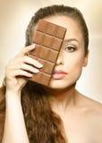 Schokolade schönes Mädchen, das hinter Schokolade, Augenschauen des Frauenmodells eins schaut Stockbild