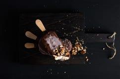 Schokolade tauchte Eis am Stiel mit abgebrochenen Nüssen auf dunklem hölzernem Brett über schwarzem Hintergrund ein Lizenzfreie Stockbilder