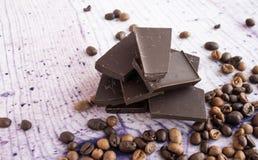 Schokolade und Kaffeebohnen auf einem purpurroten Hintergrund Lizenzfreies Stockbild