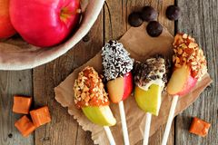 Schokolade und Karamell tauchten Apfelscheiben, Szene auf rustikalem Holz ein stockfotos