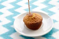 Schokolade wird auf Kuchen an der Platte auf gestreiftem Hintergrund geschüttet Stockbild