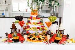 Schokoladen-Brunnen und Früchte zum Nachtisch an der Hochzeitstafel Stockfoto