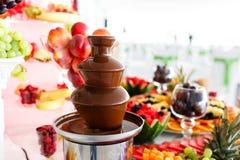 Schokoladen-Brunnen und Früchte zum Nachtisch an der Hochzeitstafel Lizenzfreie Stockfotos