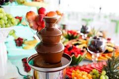 Schokoladen-Brunnen und Früchte zum Nachtisch an der Hochzeitstafel Lizenzfreie Stockbilder