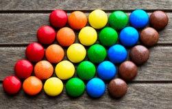 Schokoladen in der Glasur gestapelt in LGBT-Flagge auf hölzernem Hintergrund lizenzfreie stockfotografie