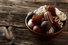 Schokoladen in der Schüssel auf dem braunen hölzernen Hintergrund Lizenzfreies Stockfoto