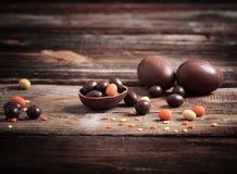 Schokoladen-Eier über hölzernem Hintergrund Stockbilder