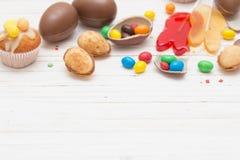 Schokoladen-Eier und kleiner Kuchen über hölzernem Hintergrund Lizenzfreie Stockfotos