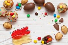 Schokoladen-Eier und kleiner Kuchen über hölzernem Hintergrund Lizenzfreie Stockbilder