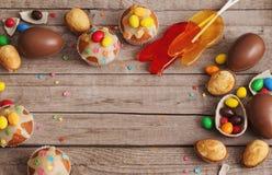 Schokoladen-Eier und Kuchen über hölzernem Hintergrund Stockbild