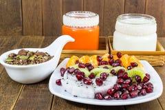 Schokoladen-Granola mit Nüssen, Mischungsfrüchten, Milch- und Karottensaft Stockfotografie