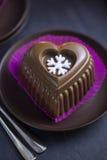 Schokoladen-Herz-Kuchen mit weißer Schneeflocke für den Silvesterabend Stockfotografie