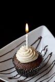 Schokoladen-kleiner Kuchen mit einer brennenden Geburtstags-Kerze Lizenzfreie Stockbilder