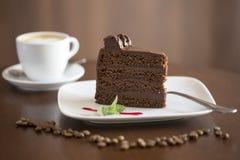 Schokoladen-Kuchen mit Kaffeetasse im Hintergrund - Scheibe Lizenzfreie Stockfotos