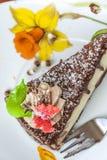 Schokoladen-Kuchen-Nachtisch und Gabel auf einer Untertasse Stockfotos