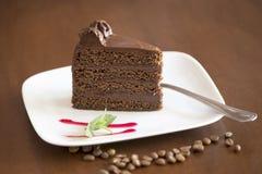 Schokoladen-Kuchen-Scheibe mit braunem Hintergrund Stockbilder