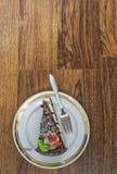 Schokoladen-Kuchen und Gabel auf einer Untertasse Lizenzfreie Stockfotografie