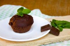 Schokoladen-Muffin mit tadellosem Blatt auf der Untertasse in der Küche Stockfoto