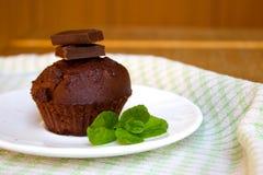 Schokoladen-Muffin mit tadellosem Blatt auf der Untertasse in der Küche Lizenzfreie Stockbilder