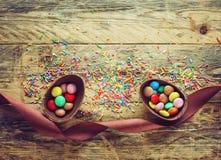 Schokoladen-Osterei mit Süßigkeit und Band Stockfotos