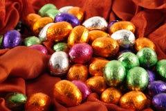 Schokoladen-Ostereier auf rotem Hintergrund Stockfotografie
