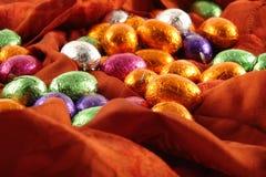Schokoladen-Ostereier auf rotem Hintergrund Lizenzfreies Stockfoto