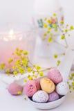 Schokoladen-Ostereier in den Pastellfarben im keramischen Löffel, brennende Kerze, weiße Serviette, Gedeck Lizenzfreies Stockbild
