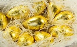 Schokoladen-Ostereier in der hellen goldenen Abdeckung Lizenzfreies Stockfoto