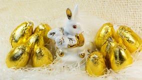 Schokoladen-Ostereier in der hellen goldenen Abdeckung um das Porzellankaninchen Stockbilder