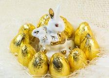 Schokoladen-Ostereier im hellen goldenen Abdeckungs- und Porzellankaninchen Lizenzfreie Stockfotos