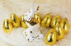 Schokoladen-Ostereier im hellen goldenen Abdeckungs- und Porzellankaninchen Stockfotos