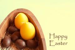 Schokoladen-Ostereier und zwei gelbe Kerzen in der hölzernen Platte Lizenzfreie Stockbilder
