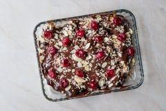 Schokoladen-Pudding-Kuchen mit Kirschen, Mandel-Scheiben und Keksen lizenzfreie stockbilder