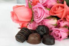 Schokoladen-Süßigkeiten und Blumenstrauß der Rosen Stockfoto
