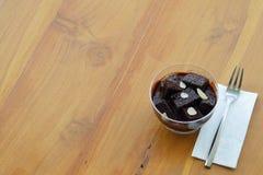 Schokoladen-Schokoladenkuchen-Pudding mit silbernem Gabel- und Seidenpapier auf hölzerner Tabelle Stockfotografie