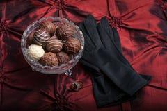 Schokoladen-Trüffeln auf einem roten Hintergrund mit schwarzen Handschuhen und Rin stockbilder