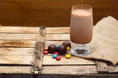 Schokoladen und heiße Schokolade auf einem hölzernen Hintergrund Lizenzfreie Stockfotos