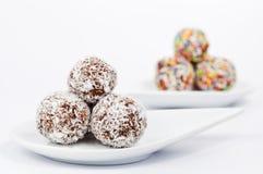 Schokoladen- und Kokosnusskugeln auf einer weißen Platte lizenzfreies stockbild