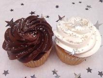 Schokoladen- und Vanillekleine kuchen mit besprüht Stockfotos