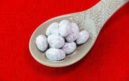 Schokoladen-und Zuckerüberzogene Mandeln auf Löffel Stockfotos