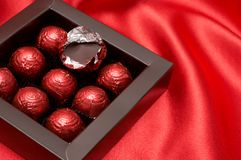 Schokoladen-Valentinsgrußtrüffeln im roten Papier Stockfotografie