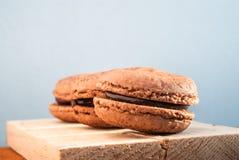 Schokoladenaroma Makrone gesetzt auf Holz und Leder Stockfoto