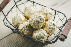 Schokoladenball mit goldener Folie in einem Korb, Weinlesefarbton Lizenzfreie Stockfotos